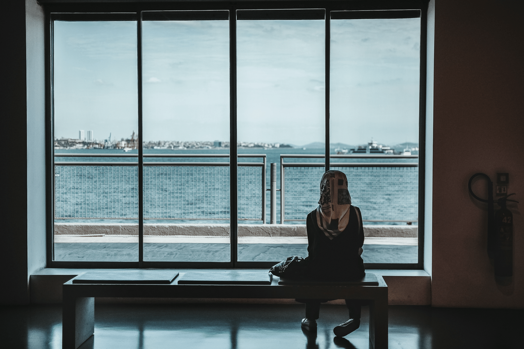Woman on bench in front of huge window